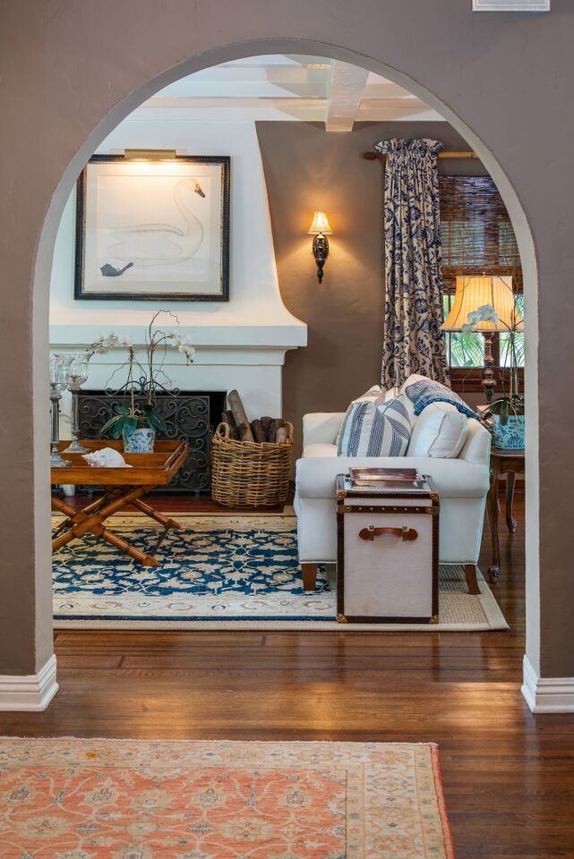 Details: old basket, bamboo/wicker coffee table, fireplace, fireplace screen, painting over fireplace, wall sconce, wall color, rug in entrance area & lamp and sofa aren't bad either. Spanish home for sale San Marino CA