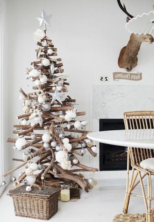 kreativer Weihnachtsbaum aus Zweigen mit weißen Dekorationen
