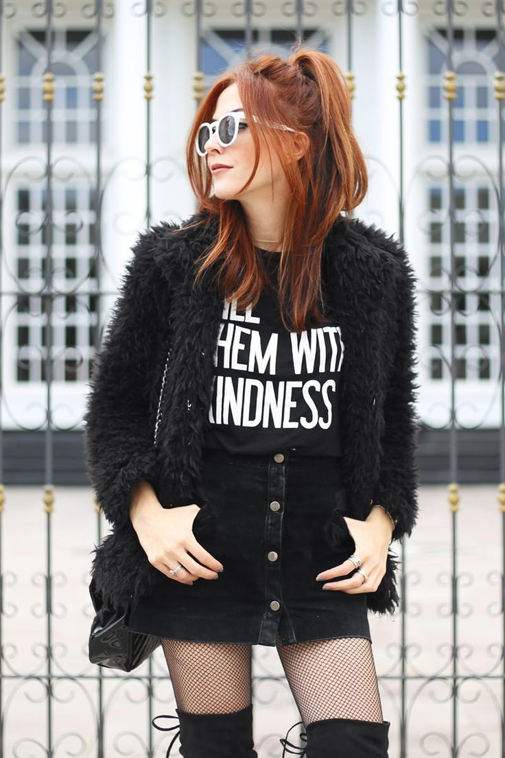 All black outfit wearing a black faux fur coat with basic tshirt and mini skirt, the perfect combo to wear with over the knee boots.