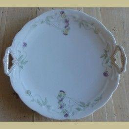 Brocante witte taartschaal met gele en paarse viooltjes     Mooie romantische taartschaal met goudkleurige versieringen op de handgreepjes.Porselein. Genummerd: zie foto 4.Doorsnede: 28 cm (incl. oortjes).Zeer lichte gebruikssporen, geen beschadigingen.
