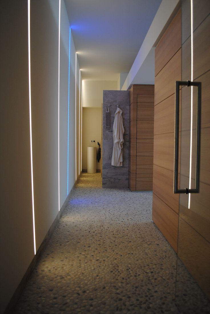 Doorloop van hal naar Wellness ruimte. Vloer gemaakt van kleine kiezelsteentjes (pebbles). In de wand zijn verschillende LED lijnen voor de sfeer een verlichting verwerkt.
