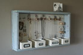Een houten kastje met klosjes om je kettingen aan te hangen en doosjes voor de losse spulletjes.