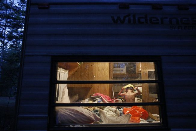Strider pulls his pajamas over his head as he changes in his grandparents' bedroom inside the cramped camper. With nowhere else to go, the Grants told the boys they were going camping and the family of four squeezed into the 24-foot camper with their cat and two dogs (Jessica Rinaldi, The Boston Globe- November 9, 2015).