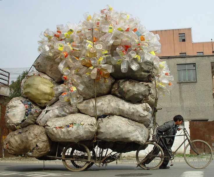 A collector pushes a tricycle loaded with bags of recyclable waste in Shanghai