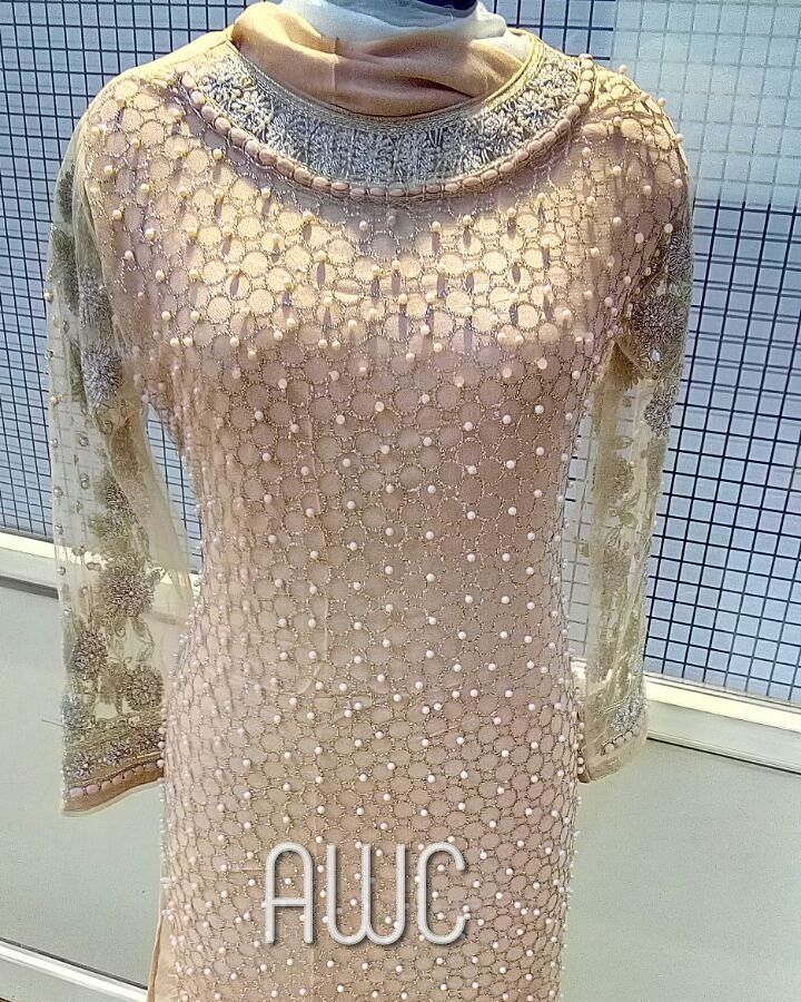 In Top Quality Imported Irish Net.  Super Heavy Designer Dress with Sea Stone and Pearl and Jari work on Neck. with golden work and pearl work all over. With Unstitch Shantoon salwar and Pure dupatta.