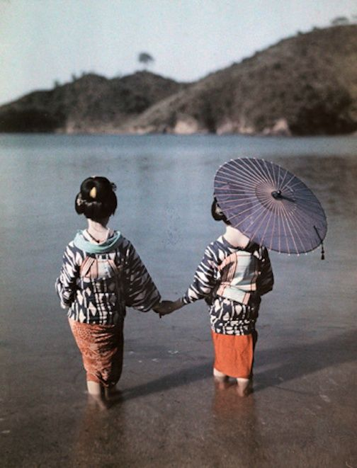 1928 Geishas walking on the beach.