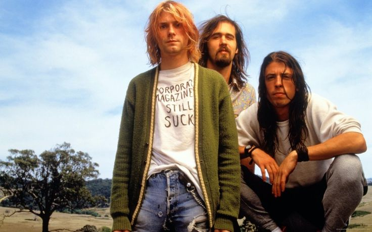 Wearing his iconic green cardigan sweater, Kurt Cobain poses with Nirvana bandmates Dave Grohl and Krist Novoseli.