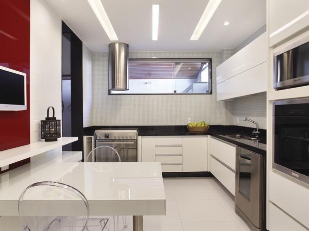 Na cozinha de base branca, um painel vermelho escuro destaca a TV Foto: Divulgação