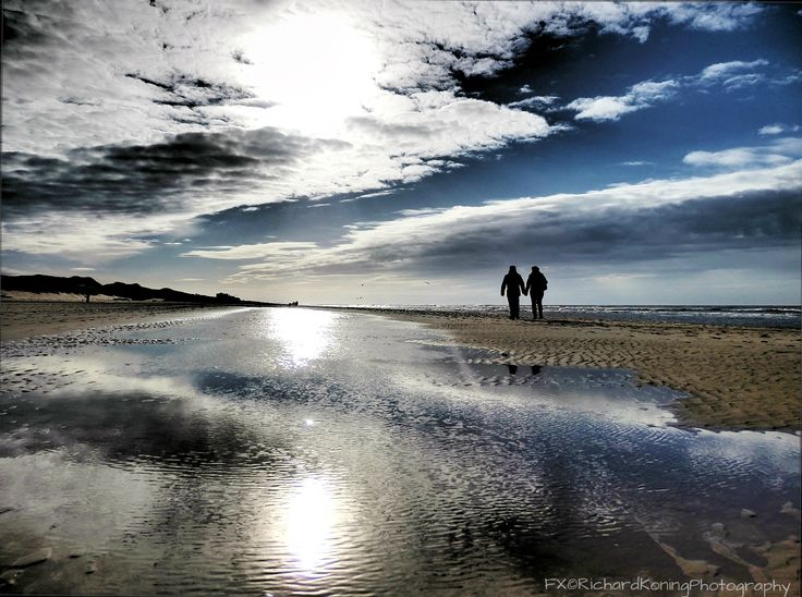 The clouds and sun reflects in the sea water near the shore.....romance at the horizon.