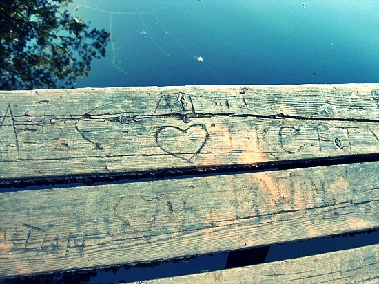 Couples carved their names into a wooden bench.