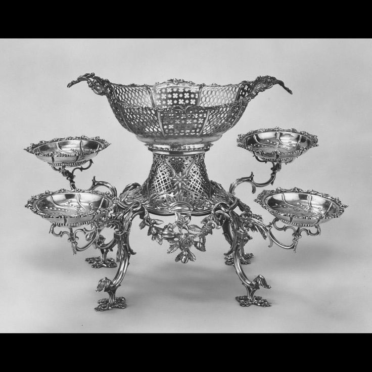 Epergne Thomas Pitts 1760s England  10 parts central basket, base, 4 arms, and 4 saucers. Boat-shaped basket at top in center of oval plan with flared rim and curved sides; body raised and pierced in alternate panels of interlacing ovals and alternating quatrefoils and stars; panels separated by chased rib; cast and applied scroll and floral border at rim; plain vertical foot fitting within rim of base; vertical rim to base with cast and applied band of alternating positive and negative…