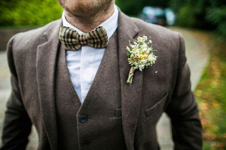 Brown tweed wool suit with plaid bow tie - Image by Navy Blur - Bride in lace wedding dress & shoes with dried flower headpiece. Groom wears tweed suit & bow tie & bridesmaids in mis-match dresses for a rustic castle, vineyard & marquee wedding with autumnal colour scheme.
