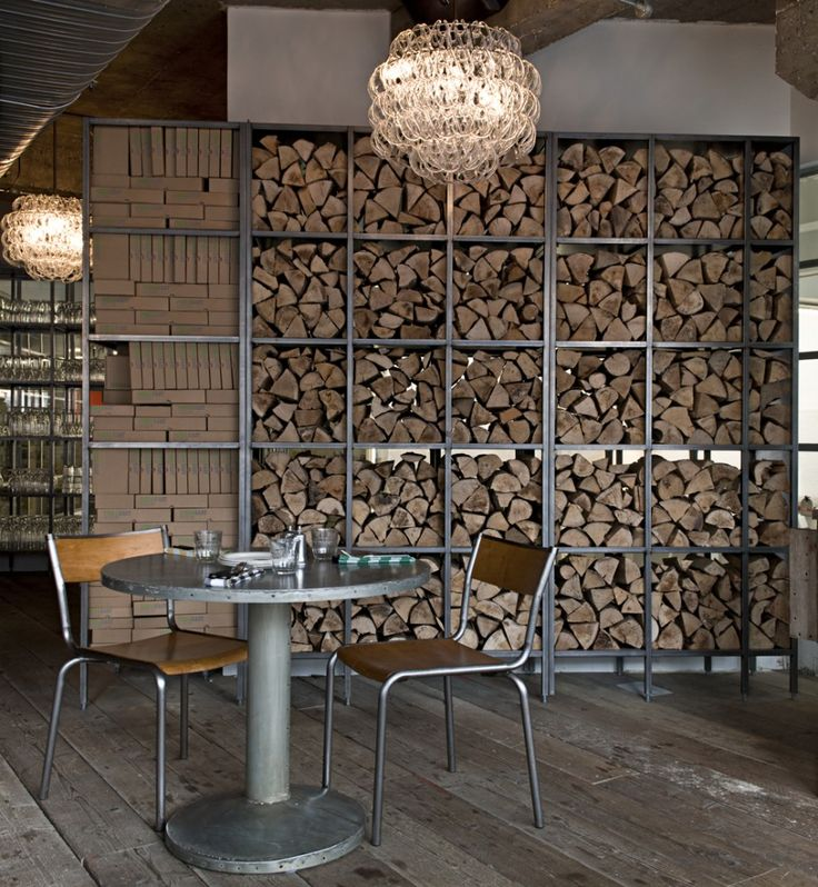 wood pile adds credibility to woodfired pizza theme as well as texture pizza east . london
