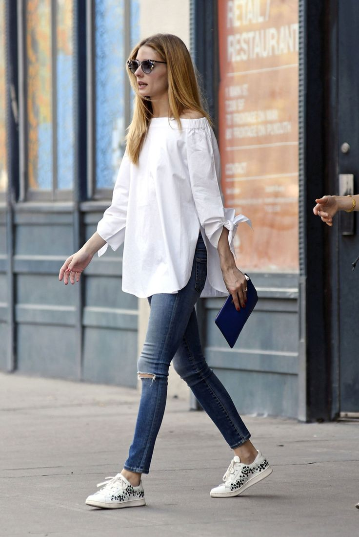 Olivia Palermo in a white off-the-shoulder top, denim jeans, floral-print sneakers and patterned sunglasses.