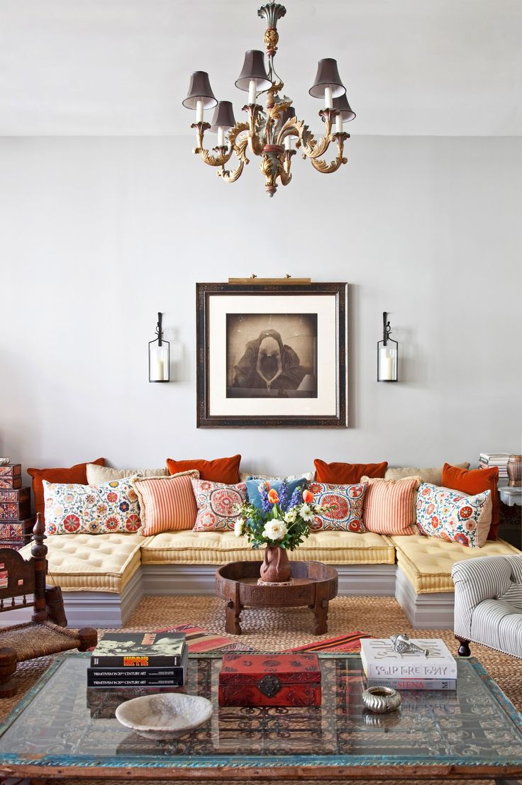 In the living space of interior designer Deborah French's eclectic Manhattan loft, she fashioned a pi-shaped sectional out of three custom mattresses upholstered in lemon-yellow damask and a wood platform. The pile of colorful pillows hails from Uzbekistan, and the cocktail table had a past life as a 19th-century Indian grain grinder.