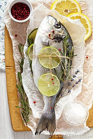 Fresh sea bream with lemon, lime, rosemary, salt and pink pepper on wooden cutting board and paper wrapping. #Fresh #sea