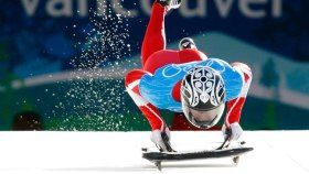 Skeleton is contested on an ice track. The athletes typically sprint alongside their sled for the first few seconds of a run, holding onto the sled with one hand before diving headfirst onto it. Positioned head-first and stomach-down, athletes will use slight shoulder, head, or body movements to steer the sled. Skeleton events are timed to the hundredth of a second (0.01).