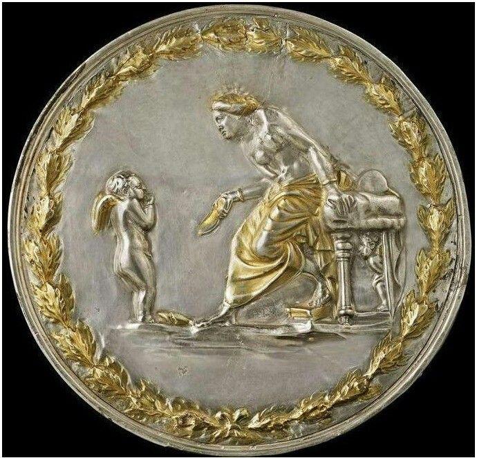 Этрусское висячее серебряное зеркало-крышка около 100 года до н.э. Чуть более подробное описание зеркала гласит: «Греческое висячее серебряное зеркало эллинистического периода около 2-1 веков до н.э. Греко-римская торевтика». Зеркало производит потрясающе впечатление. Это очень красивое изображение семейной сцены: суровая женщина угрожает расправой побоев туфлей правой ноги маленькому сыночку, сжавшемуся в комочек. Автор композиции изобразил на его спине крылышки, что сделало его ангелочком…