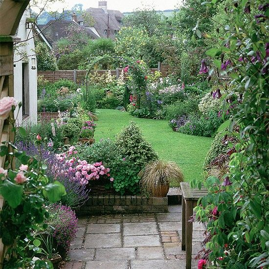 Courtyard, edged in roses, lavender and clematis, leads down to the lawn and borders planted with hardy geraniums, verbascum, and campanula.