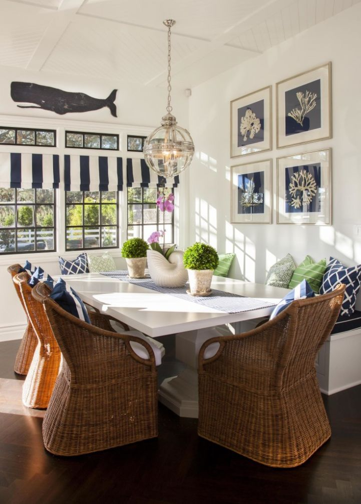 cottage breakfast nook features a navy sea prints over a built in bench facing a white dining table lined with wicker dining chairs illuminated by a