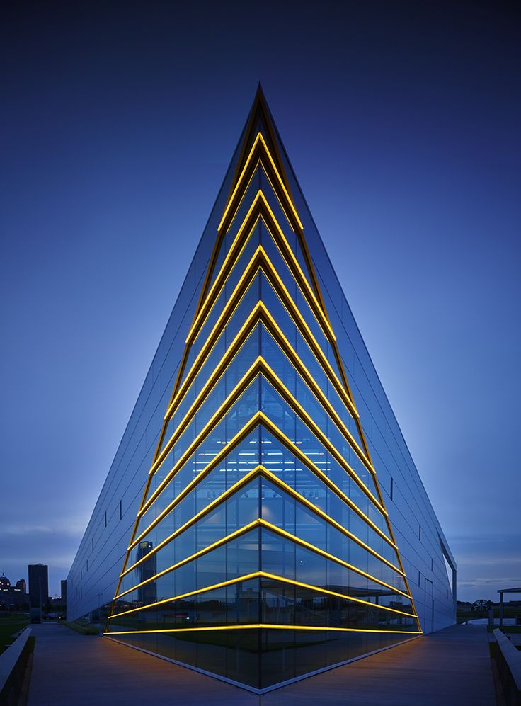 Oklahoma City Boathouse District - CHK | Central Boathouse by Elliott + Associates Architects. The river side building prow is marked by gold LED lights emphasizing form inspired by a rowing shell.  The concrete platform is within 10' of the river's edge.