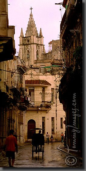 The architecture of Old Havana (Habana Vieja) Keywords: Stock Photo Picture Latin America Caribbean Habana Havana La Habana Cuba Habana Vieja Old Havana Ciudad de la Habana Cuban Tourist Attractions Verical Rain Wet Roads Bicitaxi Historical Church Old Buildings Daily Life Narrow Streets Telephoto Compressed Photo Vertical Architecture Más