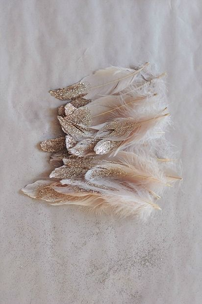 Dipping feathers in glitter can add a magical feeling to your wedding decor. Place them in your bouquet, hair, or centerpieces.