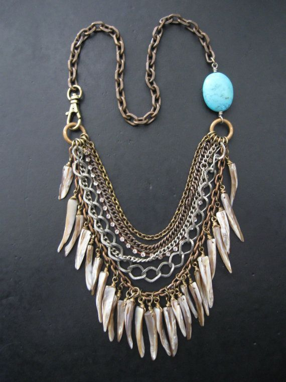 SALE SALE SALE!!!!! End of season clearance. Originally $148.    A collection of natural, earthy, khaki/grey, pearlescent shell teeth swing from a bib of mixed salvaged-vintage and new chain bits. The chains are in an assortment of metal tones including; oxidized brass, aged silver, copper, and steel tones, and are complimented with glinting strands of vintage brass rhinestone chain. Oversized brass loops rest at the collar bones. Oxidized brass chain runs around the back of the neck. A big…
