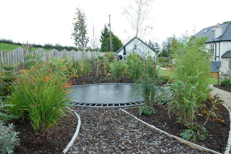 Sunken trampoline wuth wood chip and planting
