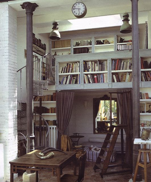 Wonderful library. It has so much I like--the gorgeous metal spiral staircase, the reading nook underneath, the worn old furniture and all the built in shelves. Want.