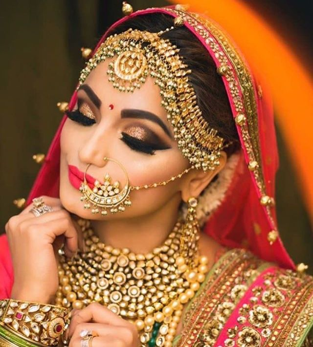 Beautiful golden jewellery on Indian bride with orange and pink lehenga.