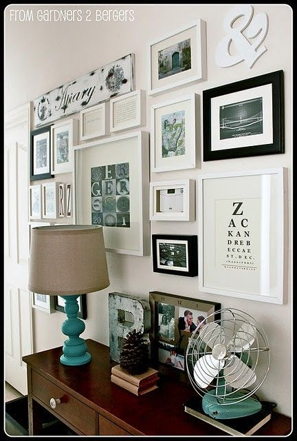 Love the different sizes/styles of frames.  Like how they framed the thermostat to incorporate it.  Like the wooden letter on table set up to work with the photo wall.