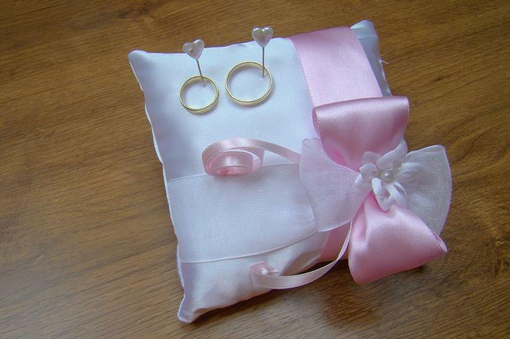 Polštářek pod prstýnky bílý Polštářek pod prstýnky z bílého saténu zdobený růžovou saténovou a bílou šifonovou stuhoua kvítkem, doplněnýbílými perleťovými špendlíky ve tvaru srdce. Rozměry cca 15 x 15 cm.
