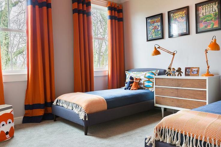 Emily Lister Interiors - Blue and orange shared boys' bedroom features framed comic book covers placed over a pair of blue linen upholstered twin beds dressed in blue bedding and an orange herringbone throw flanking a shared mid century modern dresser as nightstand topped with orange task lamps placed next to  windows dressed in bright orange curtains with blue stripes.