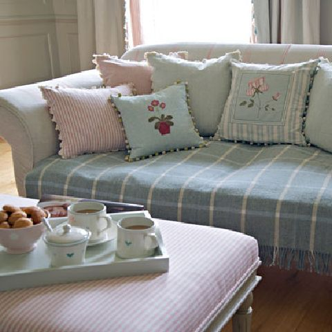 - Susie Watson Designs Fabric Collection - Neutral sofa with a blue throw with squares, cushions in pastel shades with floral and stripes and a pink striped footstool.