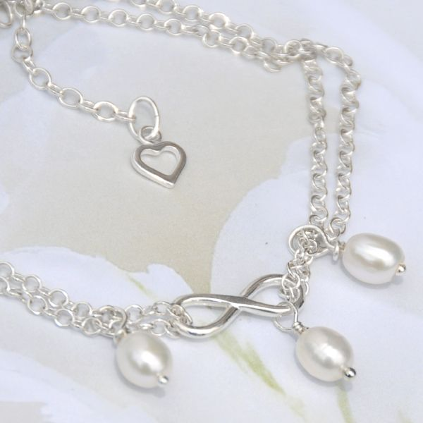 Lustrous ivory white freshwater pearls feature in this elegant minimalist design. Entirely in sterling silver, three translucent pearls hang from a double strand of sterling silver link chain with a dainty infinity focal accent.  Finished with a 2cm extension chain with a dainty open heart drop.  Eternal is so versatile, it will go with anything and looks great with everything. Wear it alone or layered with other bracelets.