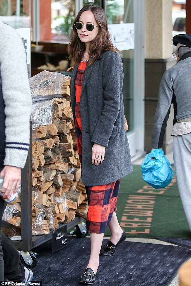 Hands-free: Dakota Johnson, 27, let her friend do the heavy lifting, leaving a grocery store in Los Angeles on Thursday with nothing in her hands as she walked a few steps behind the man