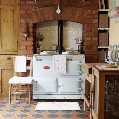 Kitchen with exposed brick fireplace chimney breast, black and red quarry tiled floor, white aga