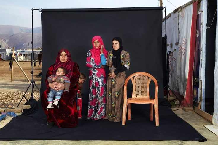 """Lost Family Portraits"" by photographer Dario Mitidieri which won third prize in the People singles category shows a portrait of a Syrian refugee family in a camp in Bekaa Valley, Lebanon, on Dec. 15, 2015. The empty chair in the photograph represents a family member who has either died in the war or whose whereabouts are unknown."