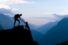image of team - Teamwork couple helping hand trust assistance silhouette in mountains sunset - JPG