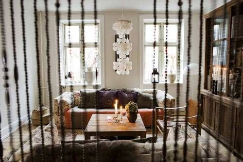 Boho apartment - natural light, comfy couch, hanging door beads, candles... So homely.