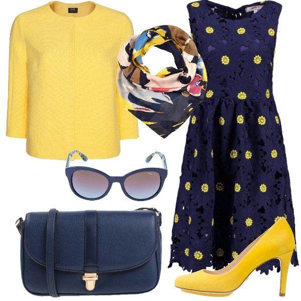 Outfit super femminile e primaverile formato da un abito con margherite blu e gialle, un blazer giallo con cerniera, una tracolla blu e un paio di décolleté gialle. Il look si completa con un foulard di seta pura colorata e un paio di occhiali con stecche decorate da fiorellini.