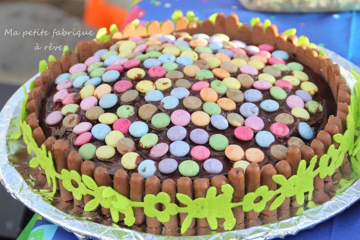 Gâteau idéal pour Pâques au chocolat décoré de smarties et entouré de biscuits fingers