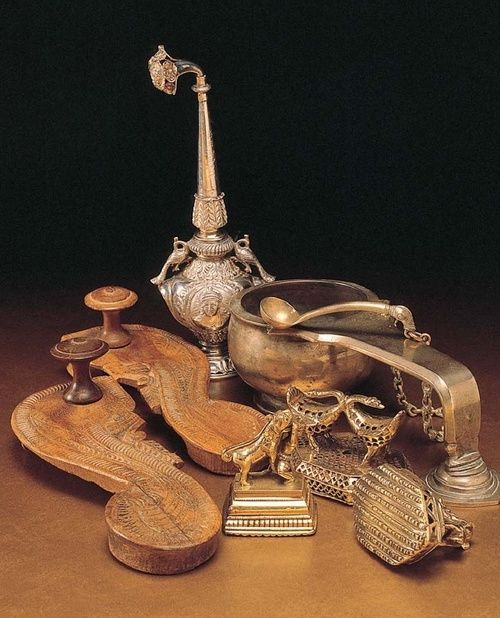 A pair of Padukas (footwear), a silver sprinkler, three brass foot scrapers, a ritual spoon, and a handled urli - vintage india