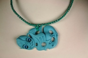 This cast resin Hei Tiki are hung from a woven plastic necklace that measures 500mm long and have paua inlaid eyes.    Truely stunning piece of New Zealand jewellery