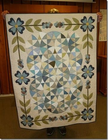 blue/green/beige quilt with floral border