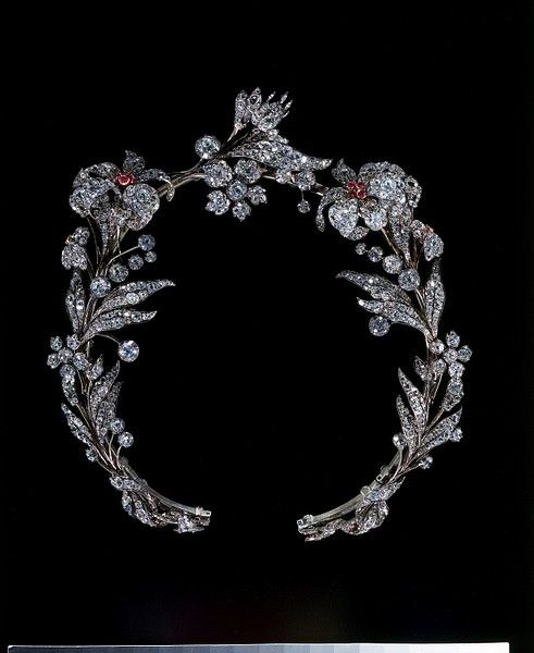 Brilliant-cut diamonds set in silver, with rubies set in gold, and a gold frame.  European. ca. 1835  Unknown maker.  Floral tiaras are very rare as they are usually broken down into separate sprays and sold as brooches. This tiara is formed of seven floral sprays. It has been worn as a necklace at some time in the past.