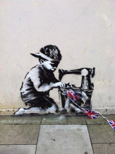 La última creación de Banksy ha aparecido en Londres, concretamente en una tienda de todo a una libra (Pounland). Se trata de un grafiti que representa a un niño de origen asiático trabajando ante una máquina de coser. Su labor, coser las banderas de Reino Unido que durante estos días están decorando las calles londinenses con motivo de los sesenta años en el trono -jubileo de diamantes- de Isabel II.