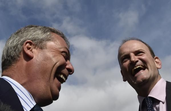 Member of Parliament (MP) Douglas Carswell (R) and Nigel Farage, the leader of Britain's UK Independence Party (UKIP) party, laugh as they walk through the town centre of Clacton-on-Sea in south east England August 29, 2014. REUTERS/Toby Melville
