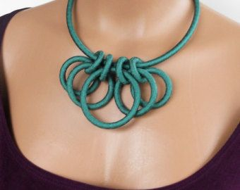 Accessorize your outfit with some Fiber Bling! Made of artisan hand dyed ribbon with black edging, this necklace is enhanced by a kumihimo cord of ribbon and black satin cord. The colors remind me of the spectrum of canna flowers, deep and bold hues that blend and create an attention getting piece. Lightweight and fun2wear.  The kumihimo cord and textile rings combined measure 21 inches long. The necklace closes with a stylish magnetic bronze end cap that makes attaching easier. The rings…